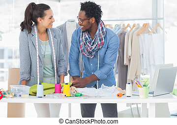 Smiling fashion designers working together