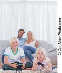 Children on the carpet playing video games in the living...