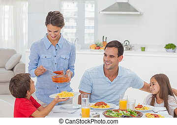 Woman giving pasta sauce to her son for the dinner