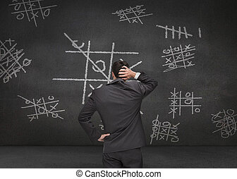 Thoughtful businessman looking at Tic-tac-toe game drawn on...