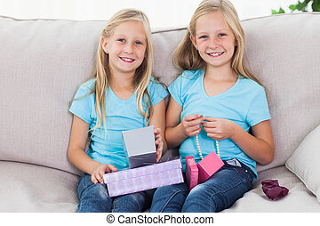 Cute twins unwrapping birthday gift sitting on a couch in...