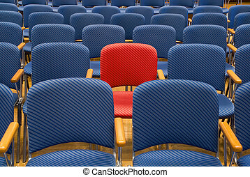 The special seat - Single red seat in the middle of rows of...