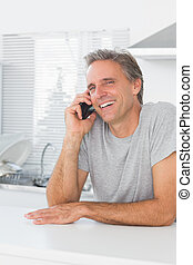 Laughing man making phone call in kitchen