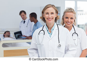 Two women doctors standing and looking at the camera in...