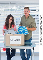Smiling volunteers taking out clothes from a donation box...