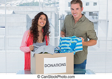 Smiling volunteers taking out clothes from donations box for...