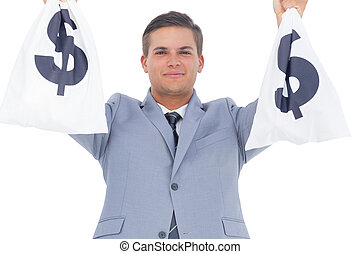 Businessman raising hands with money bags - Handsome...