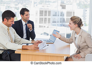 Business people laughing with interviewee in office