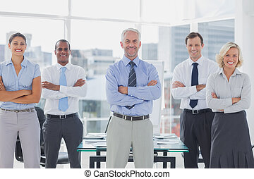Team of smiling business people standing with arms folded in...