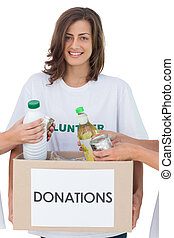 Smiling volunteer holding a food donation box