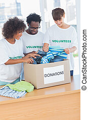 Cheerful volunteers looking at clothes from a donations box...