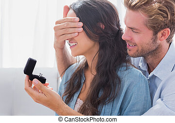 Man hiding his wife's eyes to offer her an engagement ring...