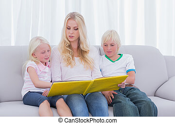 Mother reading a story to children on couch