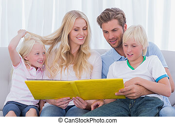 Family reading a story together sitting on the couch