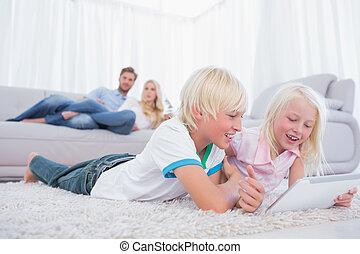 Children lying on the carpet using