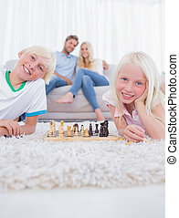 Children lying on carpet playing chess in the living room