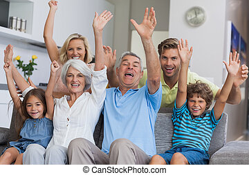 Multi-generation family raising their arms together in the...