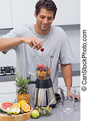 Man putting a strawberry in the blender