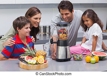 Smiling family using a blender in the kitchen
