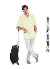 Smiling man standing with his suitcase on a white background