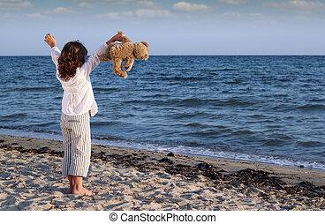 happy little girl with teddy bear on beach
