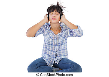 Young woman sitting on the floor listening to music