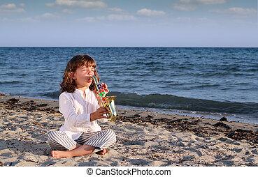 little girl play saxophone on beach