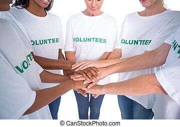 Group of female volunteers with hands together on white...
