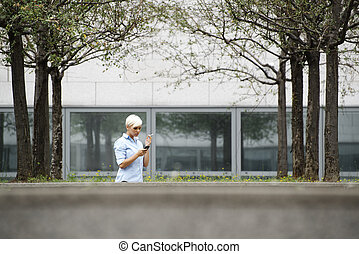 business woman smoking cigarette and typing sms on phone -...