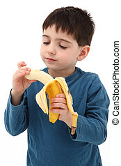 Boy Playing with Banana - Adorable five year old boy eating...