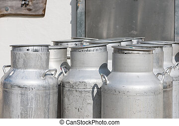 several empty silver cow milk cans with cap