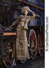 beautiful woman holding the locomotive and looks into the...