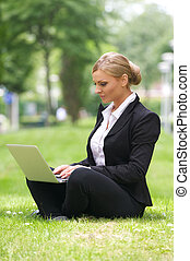 Beautiful business woman sitting with laptop in park