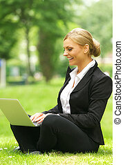 Happy business woman sitting on grass with laptop