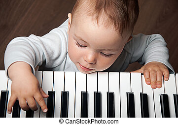 baby play music on piano keyboard - portrait of little baby...