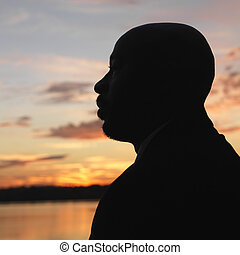 African-American man standing by water at sunset in...