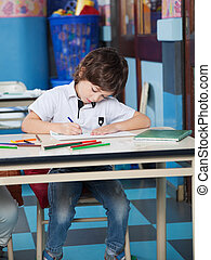 Boy With Color Pencils Drawing In Classroom