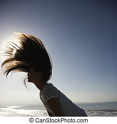 Woman swinging hair - Young Asian female swinging her hair...
