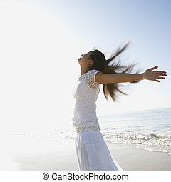 Woman with open arms. - Young Asian female at beach throwing...