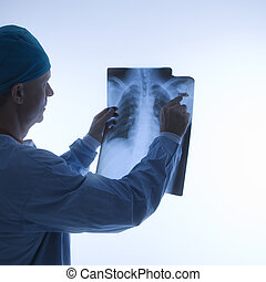 Doctor reading xray. - Mid-adult Caucasian male doctor...