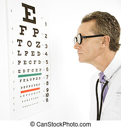 Doctor reading eye chart - Mid-adult Caucasian male doctor...