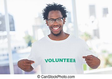 Handsome man pointing to his volunteer tshirt in a modern...