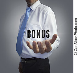 Businessman holding the word bonus on grey background