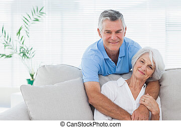 Man embracing wife who is sitting on the couch - Mature man...