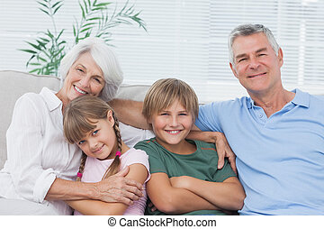 Portrait of grandparents with their grandchildren sitting on...