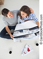 Overview of a husband and his wife holding house plan...