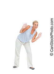 Blonde woman bending down with hands up on white background