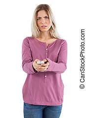 Astonished woman changing channel on a white background