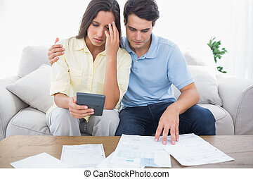 Fearful couple doing their accounts