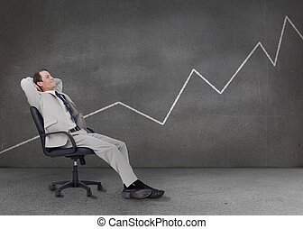 Businessman relaxing in a grey empty room